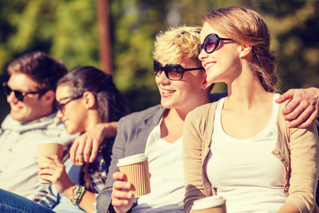 chill out: summer holidays, education, campus and teenage concept - group of students or teenagers hanging out