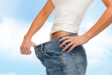 fat burning: healthcare, diet and fitness concept - close up of female showing big jeans