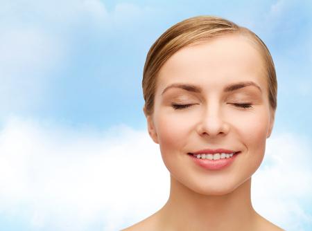 健康と美容のコンセプト - 目を閉じて美しい若い女性の顔のクローズ アップ