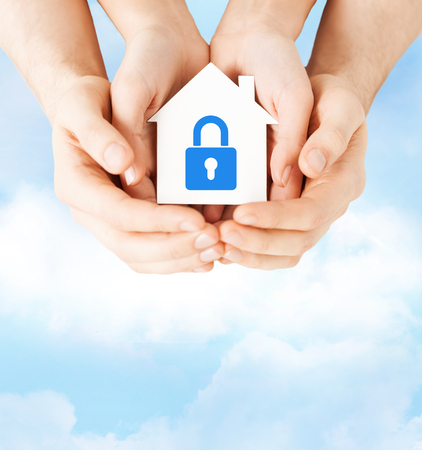 home security system: real estate and family home security concept - closeup picture of male and female hands holding white paper house with blue lock