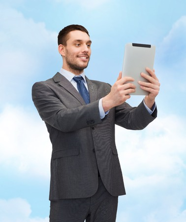 business, communication, modern technology and office concept - smiling buisnessman with tablet pc computer photo