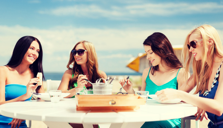 summer holidays and vacation - girls eating and drinking in cafe on the beach photo