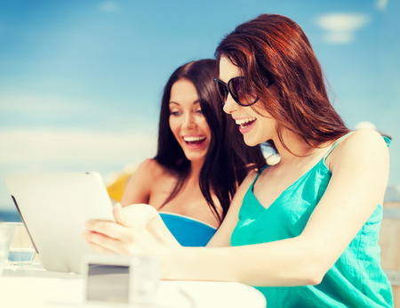 summer holidays, vacation and technology - girls looking at tablet pc in cafe on the beach photo