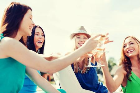 bebiendo vino: vacaciones de verano y vacaciones - muchachas con los vidrios del champán en barco o yate