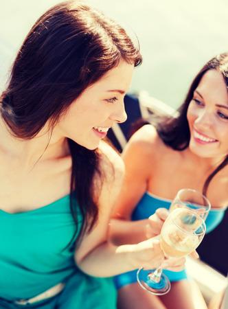 clinking: summer holidays and vacation - girls with champagne glasses on boat or yacht Stock Photo