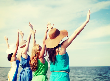 hen party: summer holidays and vacation - girls with hands up on the beach Stock Photo