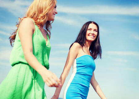 summer holidays and vacation concept - girls walking on the beach photo