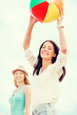 summer holidays, vacation and beach activities - girls playing ball on the beach photo
