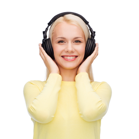 music and technology concept - smiling young woman listening to music with headphones photo