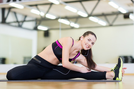 fitness, sport, training, gym and lifestyle concept - smiling teenage girl with earphones stretching on mat in the gym photo