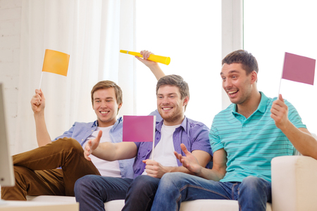 watching football: friendship, sports and entertainment concept - happy male friends with flags and vuvuzela supporting football team at home