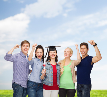 education and people concept - group of standing smiling students with diploma and corner-cap photo