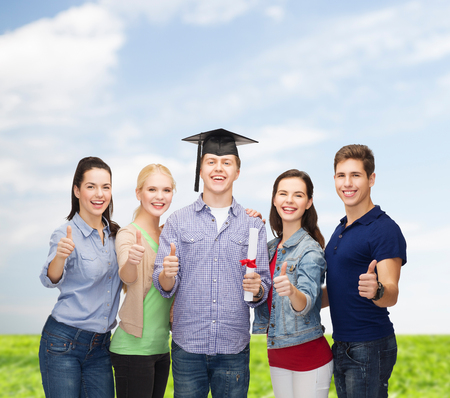 education and people concept - group of standing smiling students with diploma and corner-cap showing thumbs up photo
