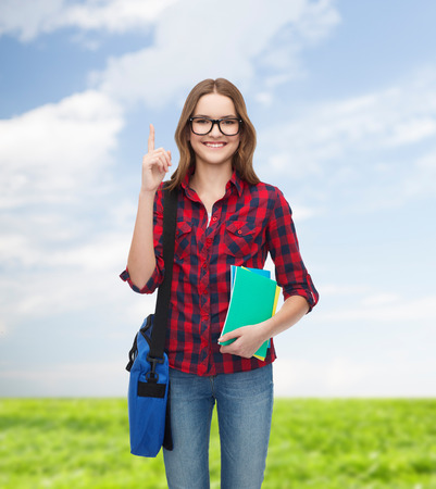 education and people concept - smiling female student in eyeglasses with bag and notebooks showing direction photo