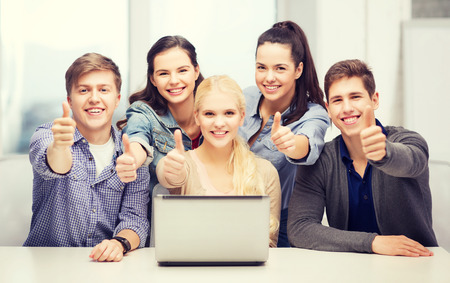 education, technology and internet concept - smiling students with laptop showing thumbs up at school photo