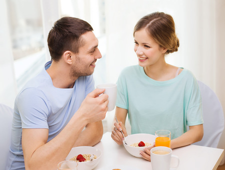 food, home, couple and happiness concept - smiling couple having breakfast at home photo