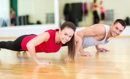push ups: fitness, sport, training, gym and lifestyle concept - smiling couple doing push-ups in the gym