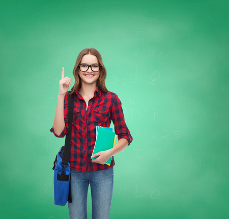 education and people concept - smiling female student in eyeglasses with bag and notebooks showing finger up on green board background photo