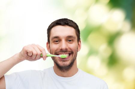 habitos saludables: hombre joven y sonriente con el cepillo de dientes - la salud y el concepto de belleza Foto de archivo