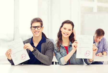 education, school and people concept - two teenagers holding test or exam with grade A photo