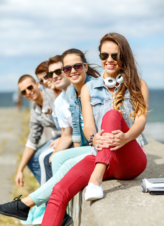 summer holidays and teenage concept - smiling teenage girl in sunglasses hanging out with friends outdoors photo