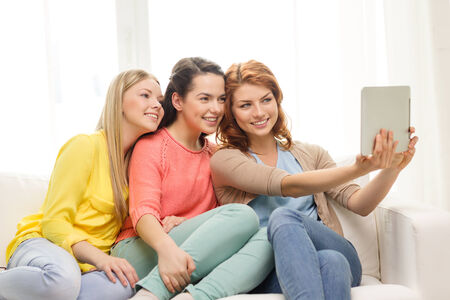 friendship, technology and internet concept - three smiling teenage girls taking picture with tablet pc computer camera at home photo