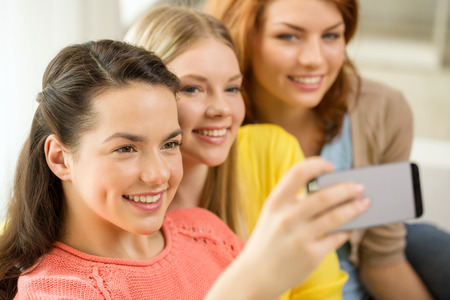 friendship, technology and internet concept - three smiling teenage girls taking picture with smartphone camera at home photo