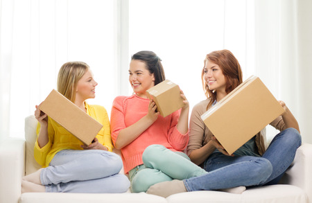 delivery room: transportation, post and friendship concept - three smiling teenage girls with cardboard boxes at home
