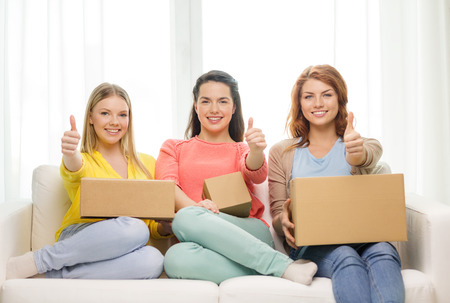 transportation, post and friendship concept - three smiling teenage girls with cardboard boxes at home showing thumbs up photo