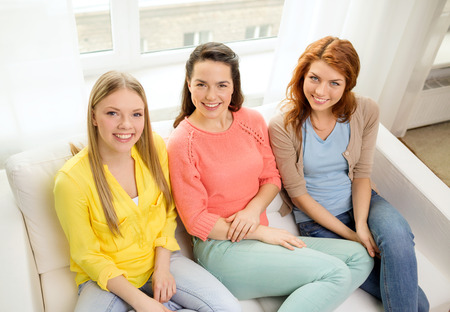 friendship and happiness concept - three girlfriends having a talk at home photo