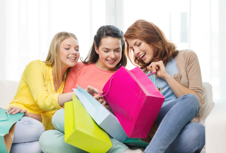shopping and lifestyle concept - three smiling teenage girls with many shopping bags at home photo