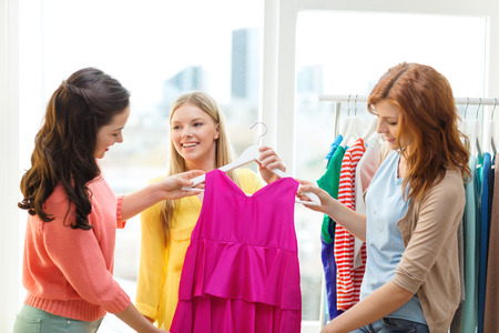 shopping, fashion and friendship concept - three smiling friends trying on some clothes at home or shopping mall photo