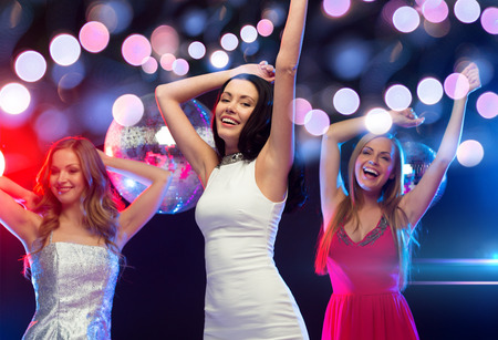 new year, celebration, friends, bachelorette party, birthday concept - three beautiful women in evening dresses dancing in the club photo