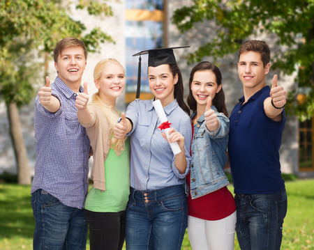 masters degree: education and people concept - group of standing smiling students with diploma and corner-cap showing thumbs up