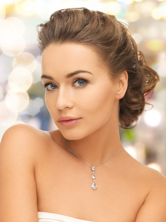 beauty and jewelry concept - woman wearing shiny diamond pendant Stock Photo