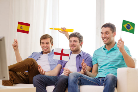 friendship, sports and entertainment concept - happy male friends with flags and vuvuzela supporting football team at home photo