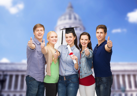 mba: education and people concept - group of standing smiling students with diploma and corner-cap showing thumbs up