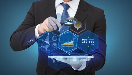 tecnologia, internet e conceito - homem negócios, segurando lupa sobre o tablet pc