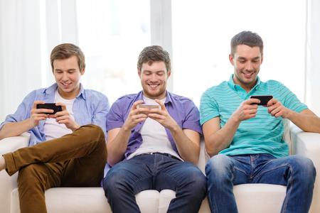 vriendschap, technologie en home concept - lachende mannelijke vrienden met smartphones thuis Stockfoto
