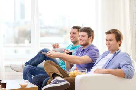 hang out: friendship, technology and home concept - smiling male friends with remote control and junk food at home