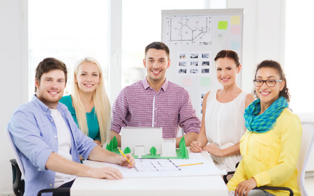 Startup education architecture and office concept smiling startup education architecture and office concept smiling architects with house model and blueprint malvernweather Choice Image