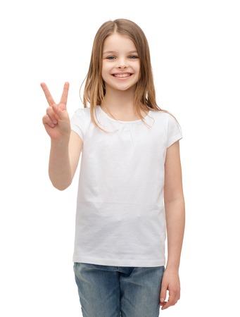 ni�as peque�as: gesto y feliz a la gente concepto - ni�a sonriente en blanco camiseta en blanco muestra gesto de paz con los dedos Foto de archivo