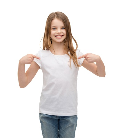 nice girl: t-shirt design concept - smiling little girl in blank white t-shirt pointing at herself