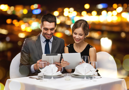 restaurant, couple, technology and holiday concept - smiling couple with menus on tablet pc computers at restaurant photo