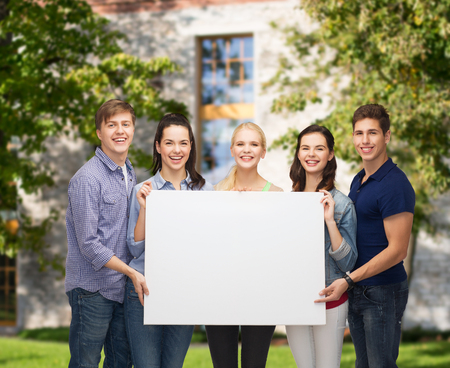 group picture: education and people concept - group of standing smiling students with white blank board