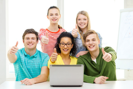 education and college concept - five smiling students with laptop at school showing thumbs up photo