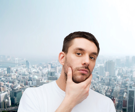 touching face: health and beauty concept - beautiful calm man touching his face