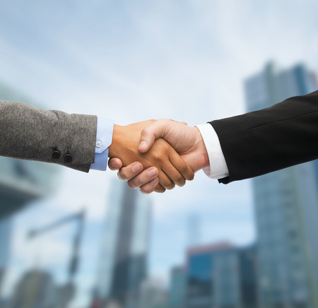 hands: business and office concept - businessman and businesswoman shaking hands