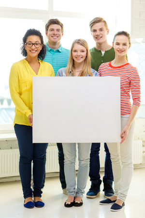 empty classroom: education, advertising and school concept - five smiling students with white blank board at school