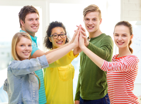 education and friendship concept - five smiling students giving high five at school photo